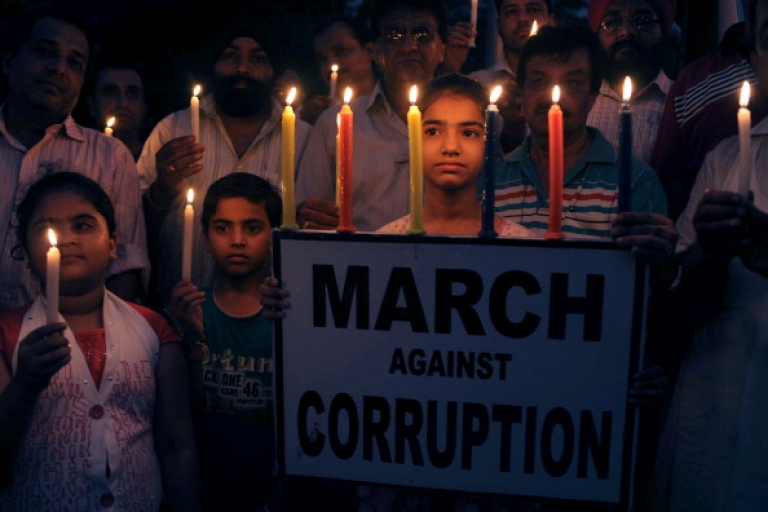 <p>Supporters of anti-corruption activist Anna Hazare hold placards and candles during a protest against corruption in Amritsar on August 23, 2011.</p>