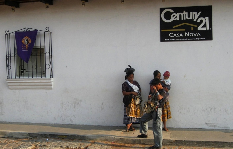 <p>Some indigenous women stand in front of a sign for a realtor company in Antigua, Guatemala. Women in Guatemala face high murder rates, although homicides declined in 2012.</p>