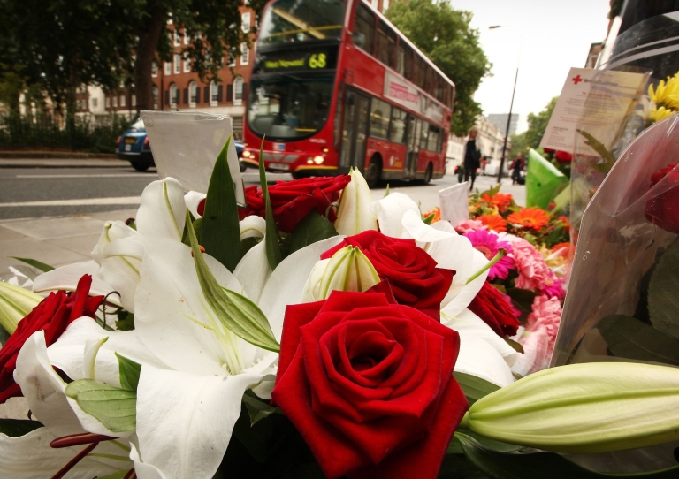 <p>A bus passes floral tributes placed next to a memorial remembering the victims of the 7/7 terrorist attacks in London.</p>