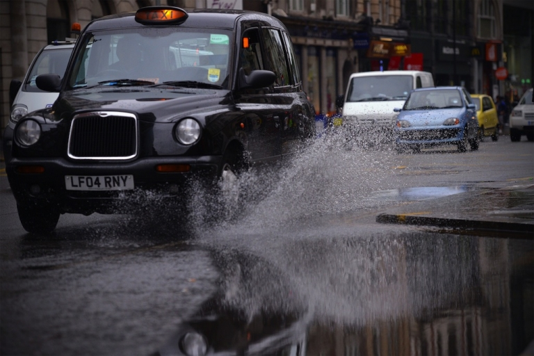 <p>A black cab drives through a puddle in central London on June 11, 2012.</p>