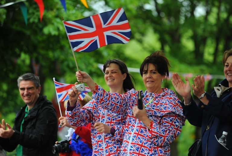 <p>Spectators dressed in the Union Flag cheer on the Olympic Flame on the Torch Relay leg between Burnley and Rawtenstall in England.</p>