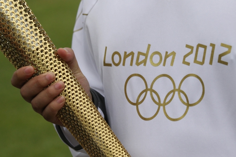 <p>An Olympic 'torch bearer' holds a London 2012 Olympic torch in Kew Gardens on April 18, 2012 in London, England.</p>