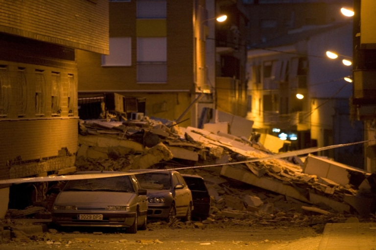 <p>View of cars crashed by debris from a collapsed building in Lorca, Spain, on May 11, 2011, after an earthquake killed at least 10 people.</p>