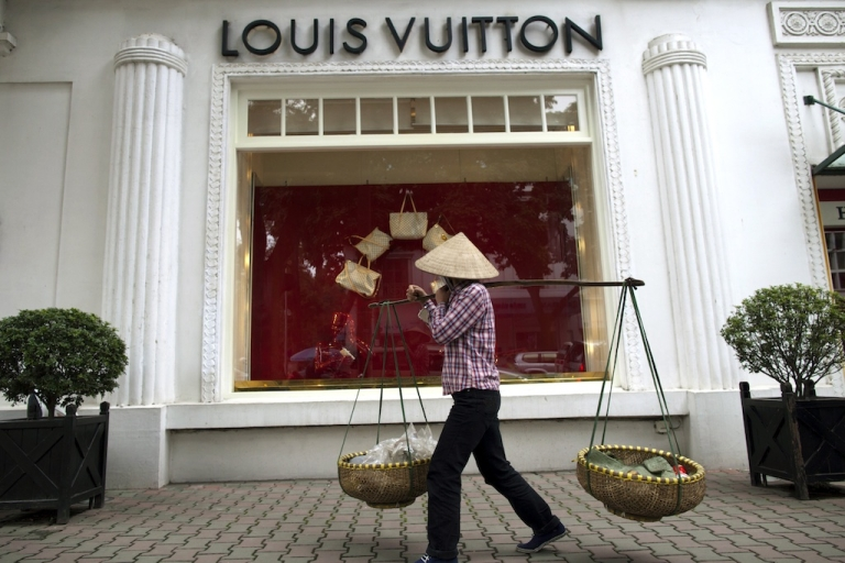 <p>A Vietnamese woman walks by the Louis Vuitton shop in the French quarter in Hanoi, Vietnam.</p>