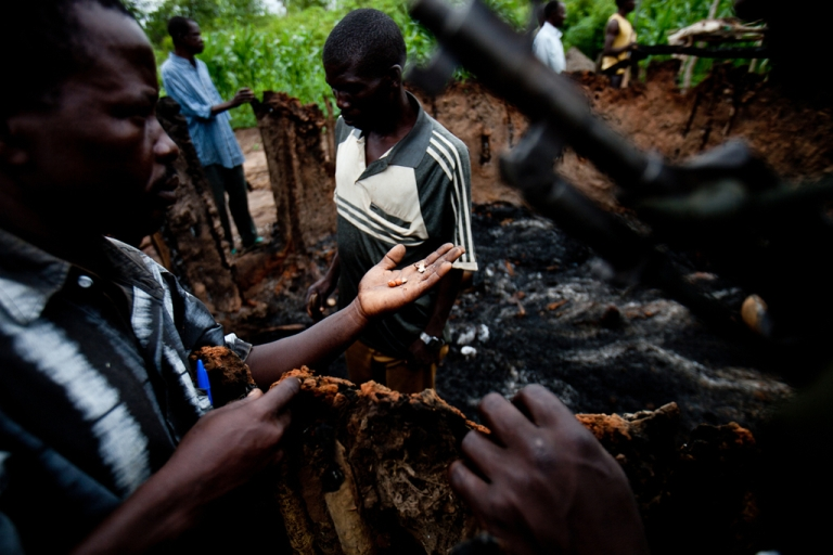 <p>The Arrow Boys are a group of South Sudanese youths who try to protect their communities from the LRA. Here a group of Arrow Boys inspect the home of Tereza Polino, near Tambura, which was burned by the LRA.</p>