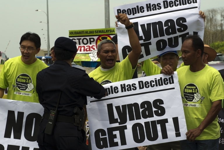 <p>A Malaysian police officer asks anti-Lynas activists to move off the road as they protest against the Lynas Corporation near the under construction Lynas plant in Gebeng, some 270 kilometers east of Kuala Lumpur on April 19, 2012. Scores of anti-lynas activists gathered to record their protest during a media tour to the plant. The Australian miner Lynas Corporation will process rare earths imported from the Mount Weld mine in Western Australia.</p>