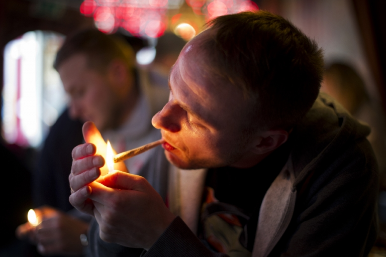 <p>Jay, a 29-year-old from London, lights a cannabis joint in a coffee shop on Nov. 1, 2012, in the center of Amsterdam, Netherlands. The ban on foreigners entering coffee shops came into effect last May in the Netherlands' southern provinces, but after intense lobbying by city authorities in Amsterdam it's now up to each city to decide how to apply the cannabis laws.</p>