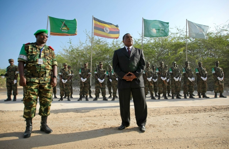 <p>Augustine Mahiga, right, Special Representative of the Secretary-General for the United Nations Political Office in Somalia (UNPOS), stands with the Deputy Force Commander of the African Union Mission in Somalia (AMISOM), Brigadier-General Audace Nduwumunsi, while addressing troops and officers at the mission's headquarters following his arrival in the Somali capital on January 24, 2012. The United Nations office for Somalia relocated from the Kenyan capital to Mogadishu, resuming operations in the war-torn Somali city after a 17-year-absence.</p>
