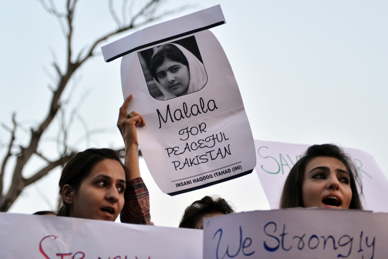 <p>Pakistani civil society activists carry placards with a photograph of the gunshot victim Malala Yousafzai as they shout anti-Taliban slogans during a protest rally against the assassination attempt on Malala Yousafzai, in Islamabad on October 10, 2012. Pakistani doctors removed a bullet from a 14-year-old child campaigner shot by the Taliban in a horrific attack condemned by national leaders and rights activists.</p>