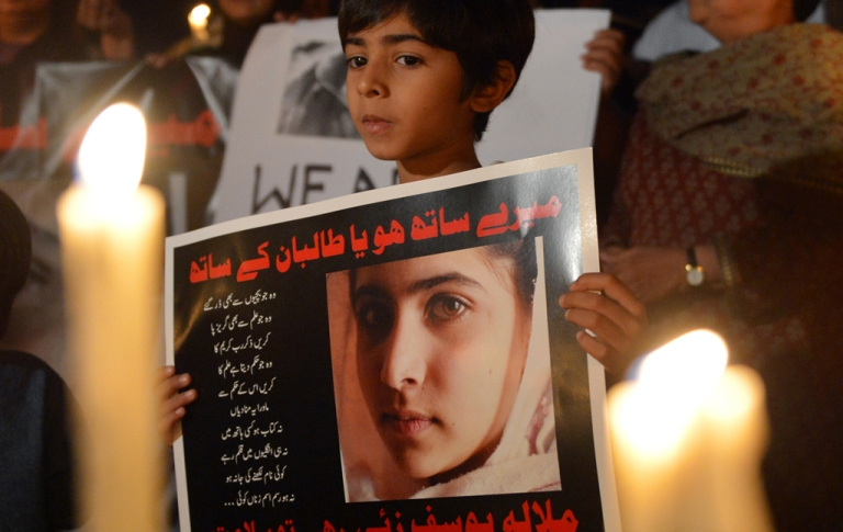 <p>Pakistanis carry candles and photographs of gunshot victim Malala Yousafzai during a protest against the assassination attempt in Islamabad on October 11, 2012.</p>