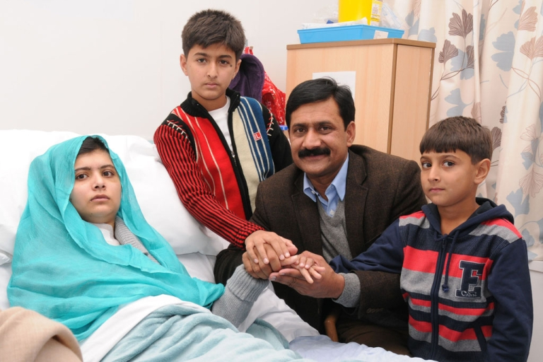 <p>In this handout photo provided by the Queen Elizabeth Hospital Birmingham, Malala Yousafzai sits with her father Ziauddin and her two younger brothers, Atal Khan, right, and Khushal Khan on October 26, 2012 in Birmingham, United Kingdom.</p>