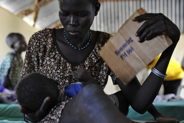 <p>A young Sudanese woman uses a piece of carton to fan her feverish son aling from malaria in South Sudan, on November 10, 2011.  One in seven children die in South Sudan before their fifth birthday, according to UN figures. In this remote village, alongside one of the world's largest freshwater marshes, the mosquito-borne disease is often deadly.</p>