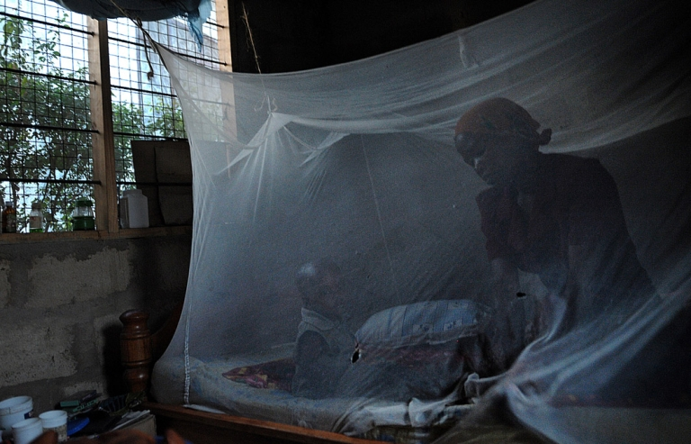 <p>A mother and her child sit on a bed covered with a mosquito net in Tanzanian  where a pioneering vaccine against malaria is in being tested at the government-run Ifakara Health Institute.</p>