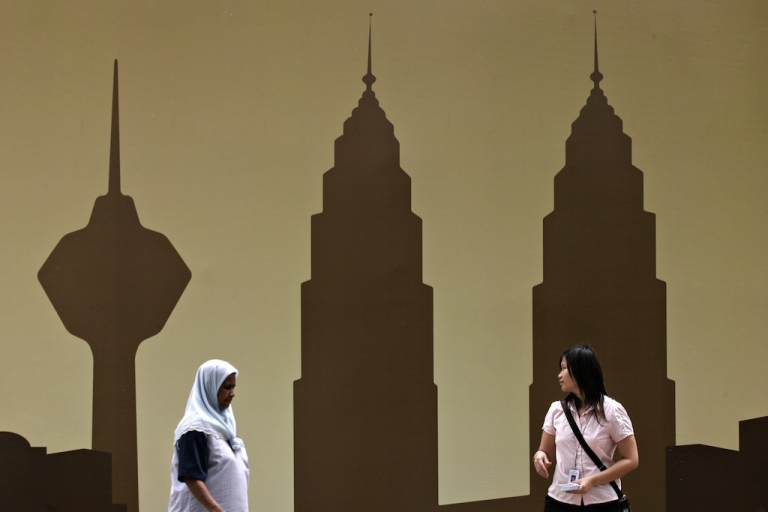 <p>Pedestrians walk past a billboard displaying the Kuala Lumpur skyline with the landmark Petronas Twin Towers (R) and the KL Tower (L) in downtown Kuala Lumpur, January 3, 2008.</p>