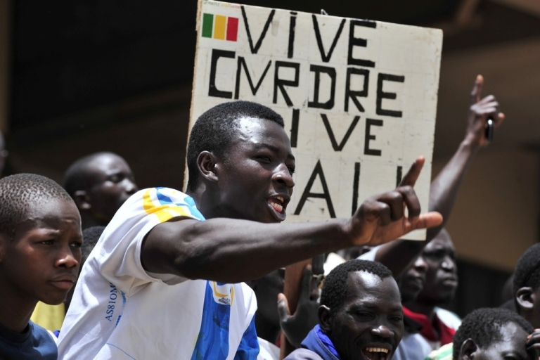 <p>Malian junta supporters shout during a meeting on March 31, 2012 in Bamako. Banner reads: '' Long live the CMRDRE. Long live Mali''.</p>