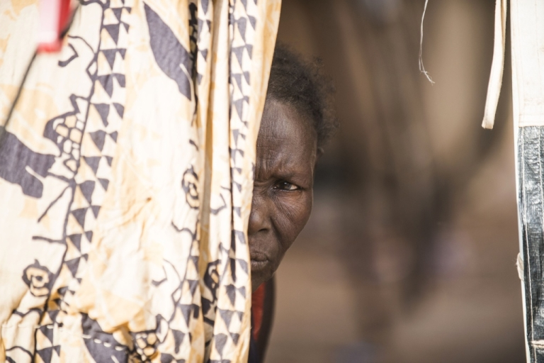<p>A woman who fled violence in northern Mali looks out from a tent at a camp for displaced people in Sevare.</p>