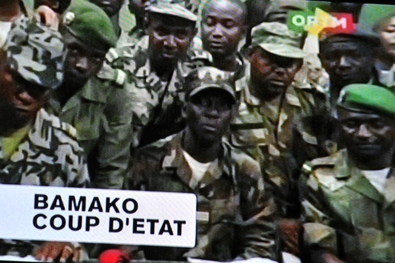 <p>Photo of a TV screen taken on March 22, 2012, shows soldiers announcing a curfew in Bamako after their military coup. The putschists, calling themselves the National Committee for the Establishment of Democracy, said the government's 'inability' to put down a Tuareg-led insurrection in the north and tackle terrorism led to their rebellion.</p>