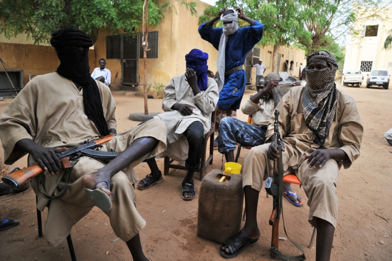 <p>A picture taken on July 16, 2012 shows fighters of the Islamist group Movement for Oneness and Jihad in West Africa (MUJAO) sitting in the courtyard of the Islamist police station in Gao.</p>