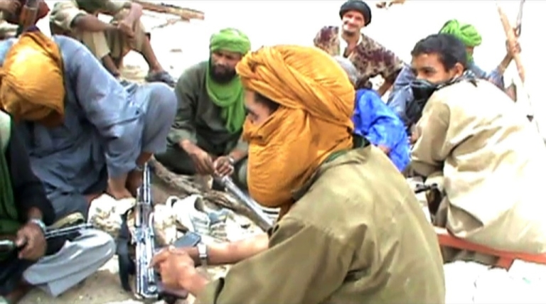 <p>A still from a video shows Islamist militants sitting on the ground with their weapons after destroying an ancient shrine in Timbuktu on July 1, 2012. Islamist rebels in northern Mali smashed four more tombs of ancient Muslim saints in Timbuktu on July 1.</p>