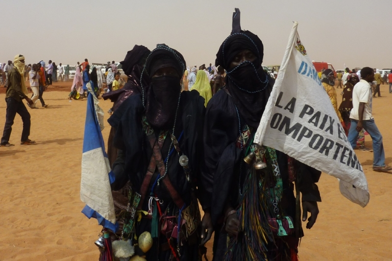 <p>Ex-members of the Tuareg rebellion hold a sign which reads 'Peace is an attitude', at the 'Forum for Peace and Development', on January 22, 2012, in Arlit, a city know for its uranium mining. Addressing the Forum, Niger's President Mahamadou Issoufou warned of a new Tuareg rebellion in the north of the country after clashes between soldiers and rebels in neighboring Mali.</p>