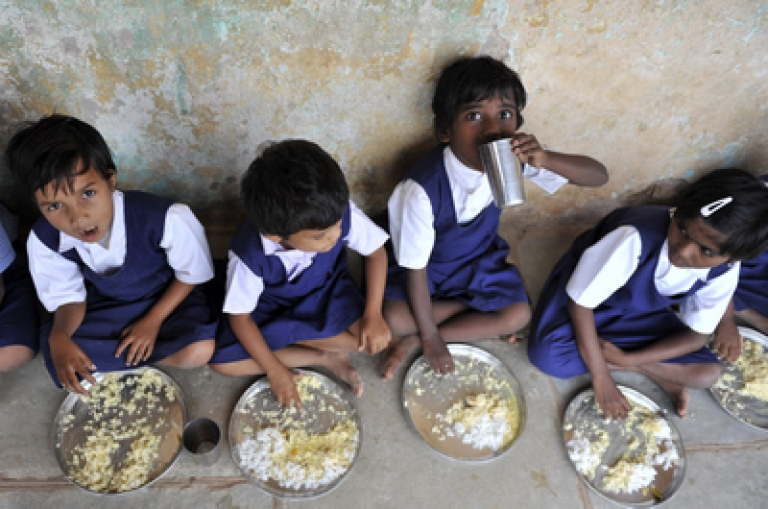 <p>Indian schoolchildren eat food served  as part of The 'Mid Day Meal' scheme at a Government Primary School in Hyderabad on June 23, 2010.  The scheme is the popular name for the school meals programme in India. It involves provision of lunch free of cost to schoolchildren on all working days. The key objectives of the programme are: protecting children from classroom hunger, increasing school enrolment and attendance, improved socialisation among children belonging to all castes, addressing malnutrition, and social empowerment through provision of employment to women.</p>