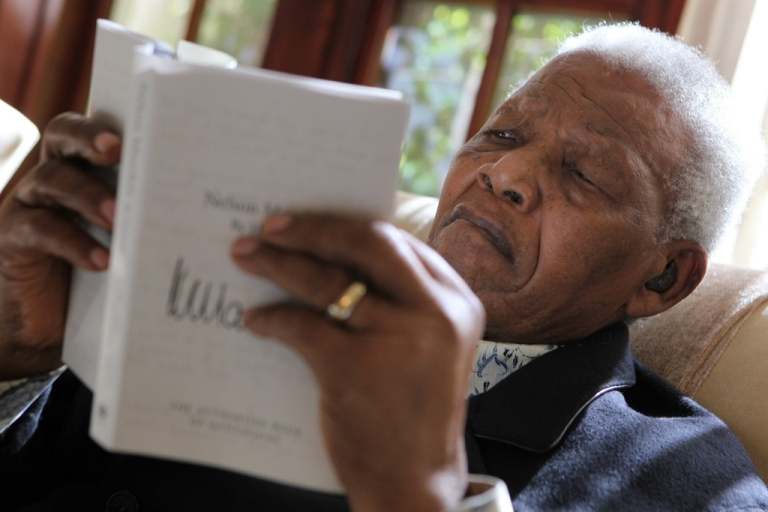 <p>Nelson Mandela looks at a copy of his latest book