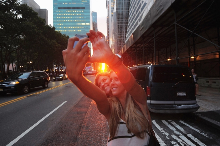 <p>Two women photograph themselves during the Manhattanhenge sunset in New York City on July 13, 2011.</p>
