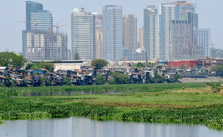 <p>Squatter shanties perch precariously along waterways in Manila on March 17, 2011</p>