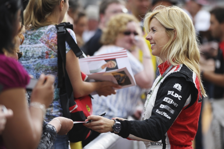 <p>Maria de Villota of Spain signs autographs during previews to the Monaco Formula One Grand Prix in Monte Carlo on May 25, 2012.</p>
