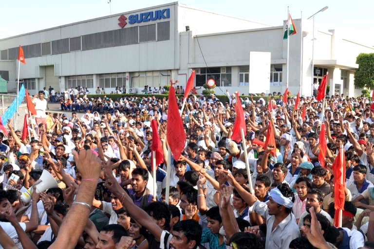<p>Indian workers shout slogans as they wave flags outside a Maruti-Suzuki vehicle plant at Manesar, on the outskirts of New Delhi on October 14, 2011. 40 people were injured and one killed in clashes between the protesting workers and managers and executives on July 18, 2012 at the same plant.</p>