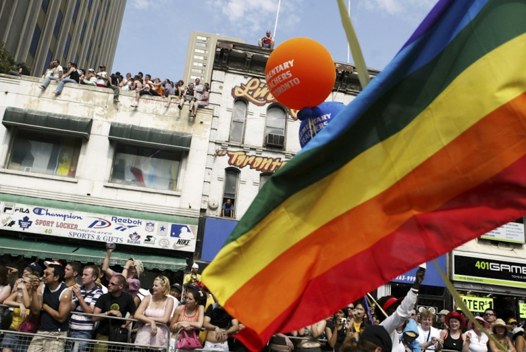 <p>Thousands of people line the streets and rooftops of buildings during the annual Pride Parade in Toronto, Canada. The parade attracts around 800,000 spectators annually, celebrating gay and lesbian diversity.</p>