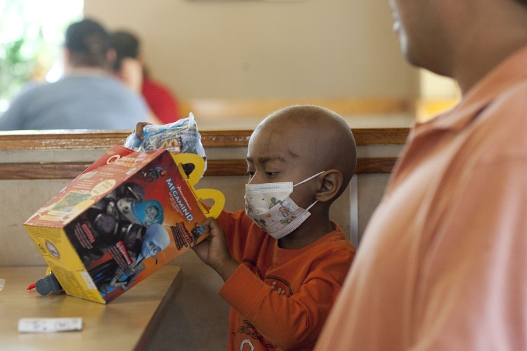 <p>Five-year-old Andy Villatoro plays with a toy he received after ordering a Happy Meal at McDonald's as his father Carlos Villatoro (R) watches on Nov. 3, 2010 in San Francisco, California.</p>