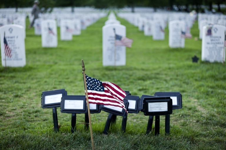 <p>A flag is seen at the temporary marker for a mass grave in Section 60, an area largely used for those who died while serving in the wars in Afghanistan and Iraq, at Arlington National Cemetery May 24, 2012 in Washington, DC, ahead of Memorial Day on May 28, 2012.</p>