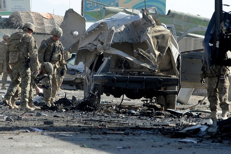 <p>US soldiers inspect the site of a suicide attack near the gate of Kandahar international airport on January 19, 2012.  A suicide bomber killed at least seven people and wounded eight on January 19 in an attack at Kandahar international airport in war-torn southern Afghanistan, officials said.</p>