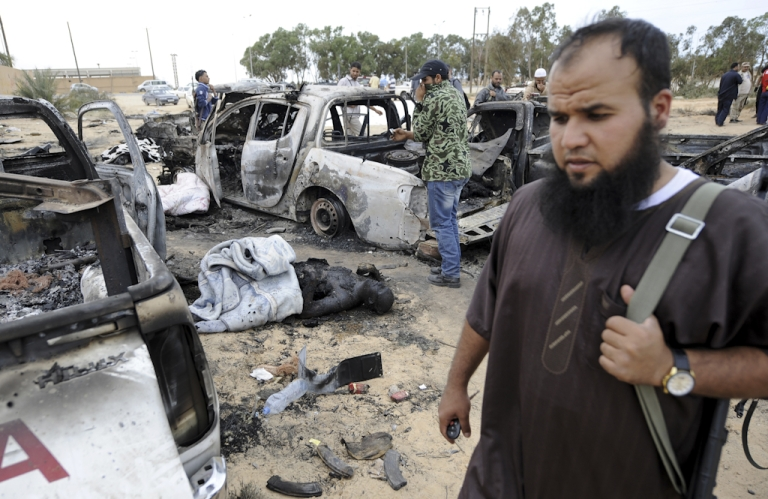 <p>Libyan National Transitional Council (NTC) fighters walk past a charred corpse at the site where a convoy of loyalist forces is believed to have been bombed by NATO before the killing of Muammar Gaddafi in Sirte on October 22, 2011.</p>