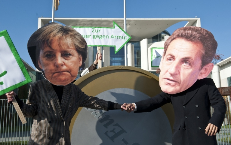 <p>Protesters dressed as German Chancellor Angela Merkel and French President Nicolas Sarkozy stage a demonstration in front of the chancellery in Berlin October 21, 2011.</p>