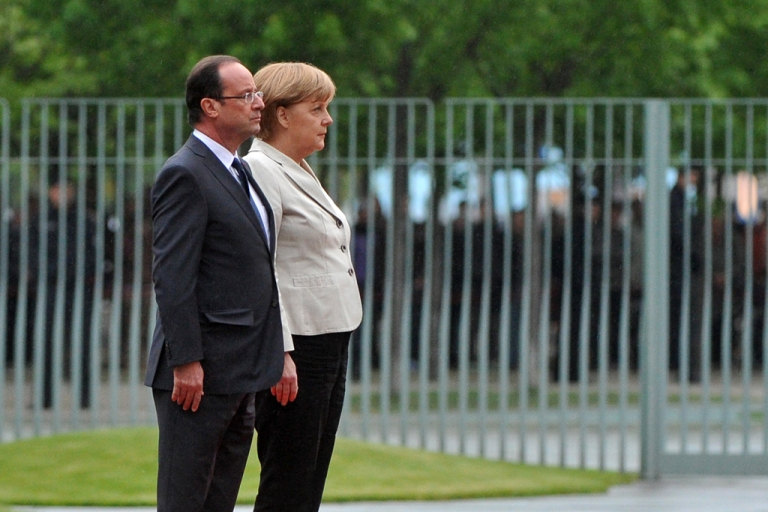 <p>German chancellor Angela Merkel (R) and the new French president Francois Hollande listen to their national anthems at the German Chancellery on May 15, 2012 in Berlin. Francois Hollande meets Angela Merkel for their first talks on the debt crisis as Greece's future in the eurozone appears uncertain before giving a news conference and sharing a working dinner.</p>