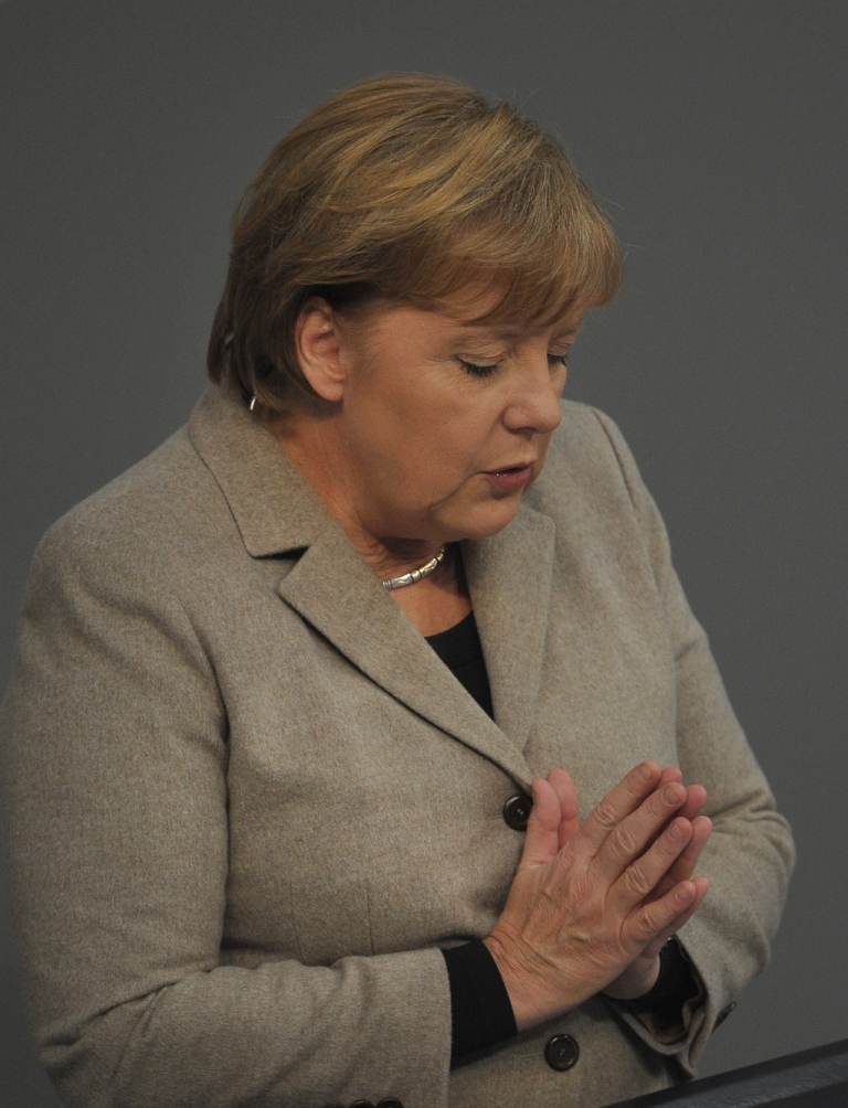 <p>German Chancellor Angela Merkel strikes a prayerful pose in the Bundestag today - as well she might - given the news from Europe's stock markets.</p>