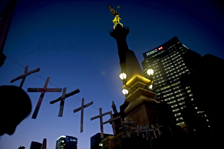 <p>A member of the Movement for Peace with Justice and Dignity hangs crosses in an altar in memory of more than 40,000 victims of violence in Mexico City. Another member of the peace movement, Trinidad de la Cruz Crisostomo, was found murdered today.</p>