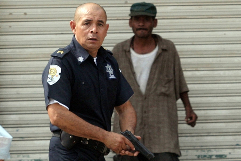 <p>A municipal police officer chased members of a gang in Acapulco, Mexico, on January 8, 2011, after twenty-five bodies were found in the city. Ten more dead were found there on June 9, and over 40,000 people in Mexico have been killed in drug-related violence since December 2006, a surge that many are attributing to lose US gun laws.</p>