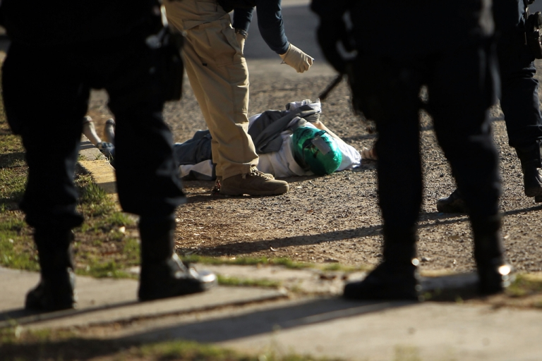 <p>A criminal investigators takes pictures of a body with a mask in the street, one of numerous murders over a 24 hour period, on March 26, 2010 in Juarez, Mexico.</p>