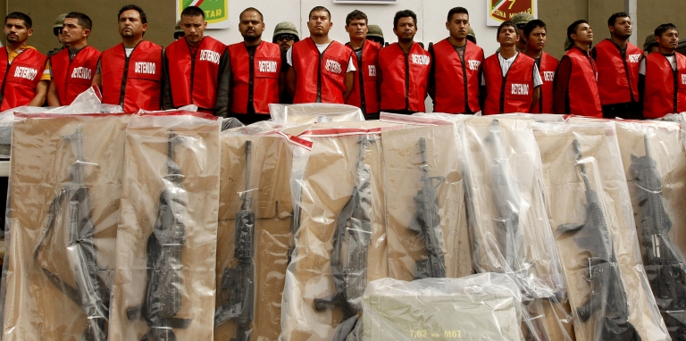 <p>Fourteen alleged members of Los Zetas drug cartel and seized weapons are presented to the press in Monterrey, Mexico on Feb. 15. Many Mexicans wonder why the country cannot return to the peaceful days when governments struck deals with cartels.</p>