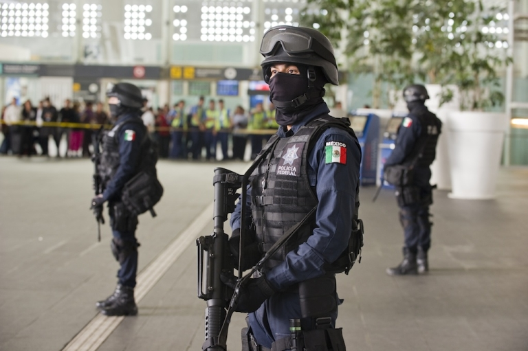 <p>Federal police officers stand guard outside the food court of Mexico City International Airport after the deadly June 25 shootout.</p>