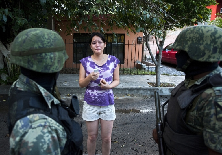<p>Mexican soldiers listen a distressed woman near Televisa TV network where a car bomb exploded early Friday in the northeastern city Ciudad Victoria, Tamaulipas state on Aug. 27, 2010. The Gulf of Mexico drug cartel was then engaged with the Zetas drug cartel in a bitter turf war for control of Tamaulipas smuggling routes into the United States.</p>