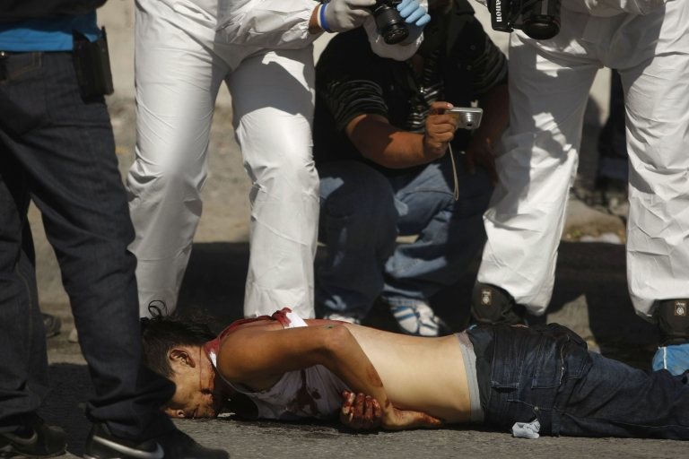 <p>Forensic personnel take pictures of a corpse on a street in Monterrey, Mexico on April 21, 2012.</p>