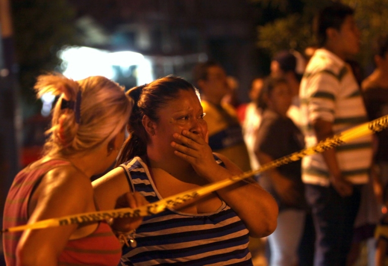 <p>Two women react after seeing the bodies of two of four men killed on a street in Monterrey, Nuevo Leon state, Mexico, on June 18, 2012. More than 50,000 people have been killed since President Felipe Calderon launched a crackdown on the drug cartels in December 2006.</p>