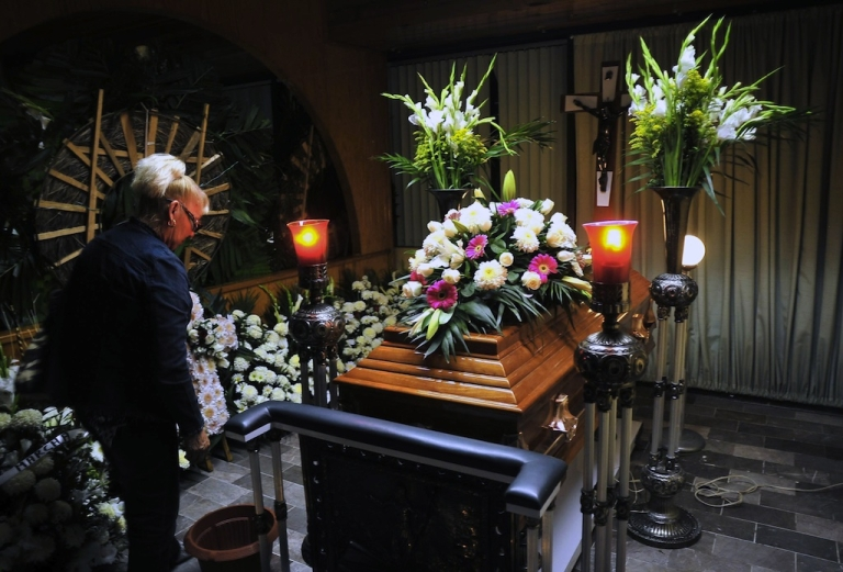 <p>A woman stands next to the coffin of Mexican journalist Regina Martinez, in Xalapa, Veracruz State, Mexico, on April 29, 2012. Martinez, a crime reporter for national magazine Proceso, was found dead in her house last month.</p>