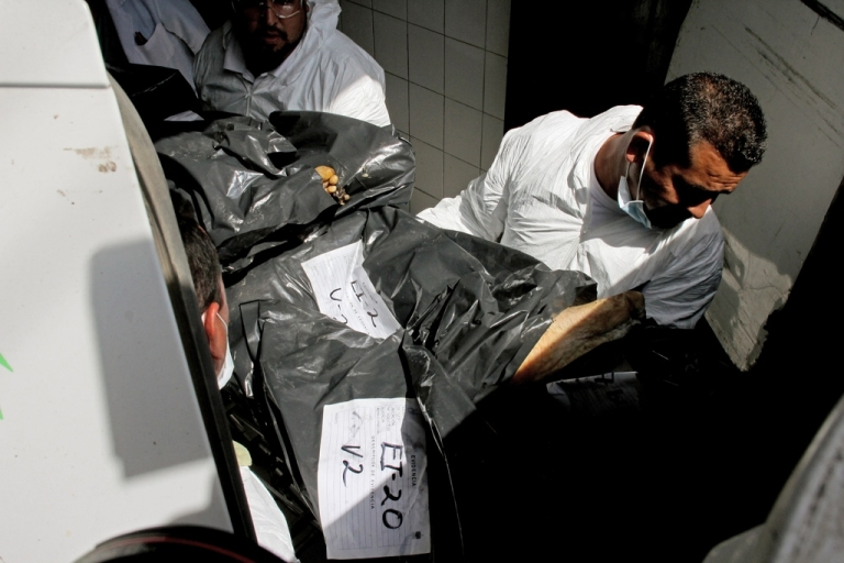 <p>Forensic technicians unload from a van to the morgue, some of the 15 corpses found earlier on May 9 in two abandoned vehicles on the highway to Chapala.</p>