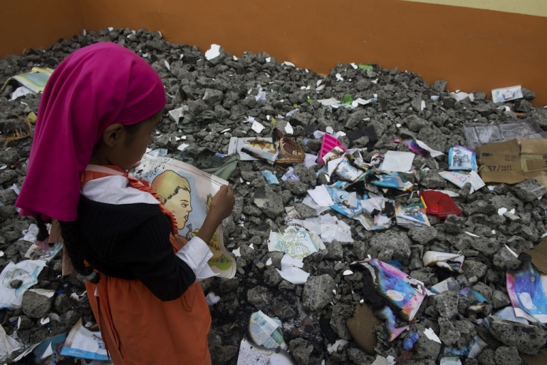 <p>A girl wearing the style of clothes required by the Virgin of the Rosary sect in the Mexican state of Michoacan walks through the rubble of a primary school on July 18, 2012. The building was destroyed by conservative followers of the group, who claimed mainstream schools were introducing vice into their community.</p>