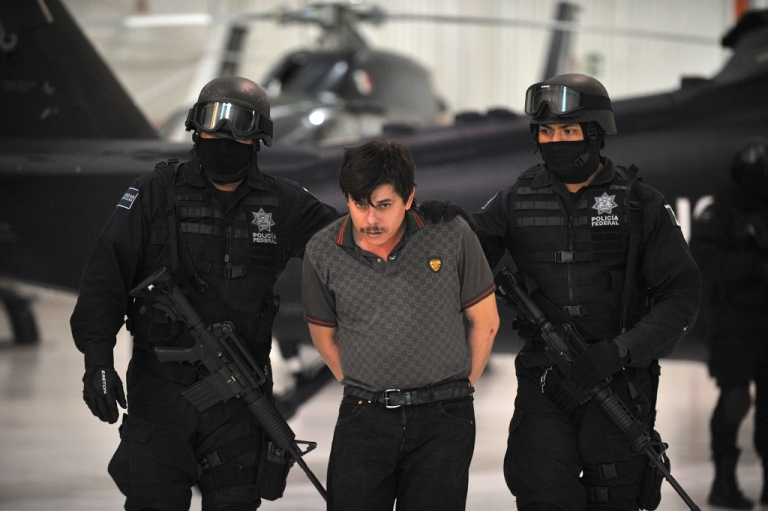 <p>Mexican police escort Jaime Herrera Herrera, 'El Viejito', an alleged member of the Joaquin 'El Chapo' Guzman's drug smuggling cartel, to be photographed by the media in Mexico City on Feb. 14.</p>